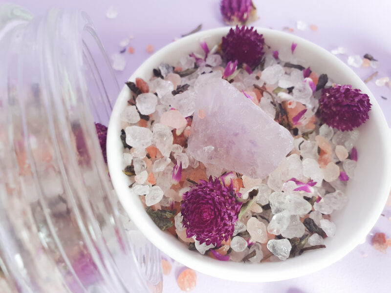 A picture of bath salts in a bowl with an amethyst in the middle
