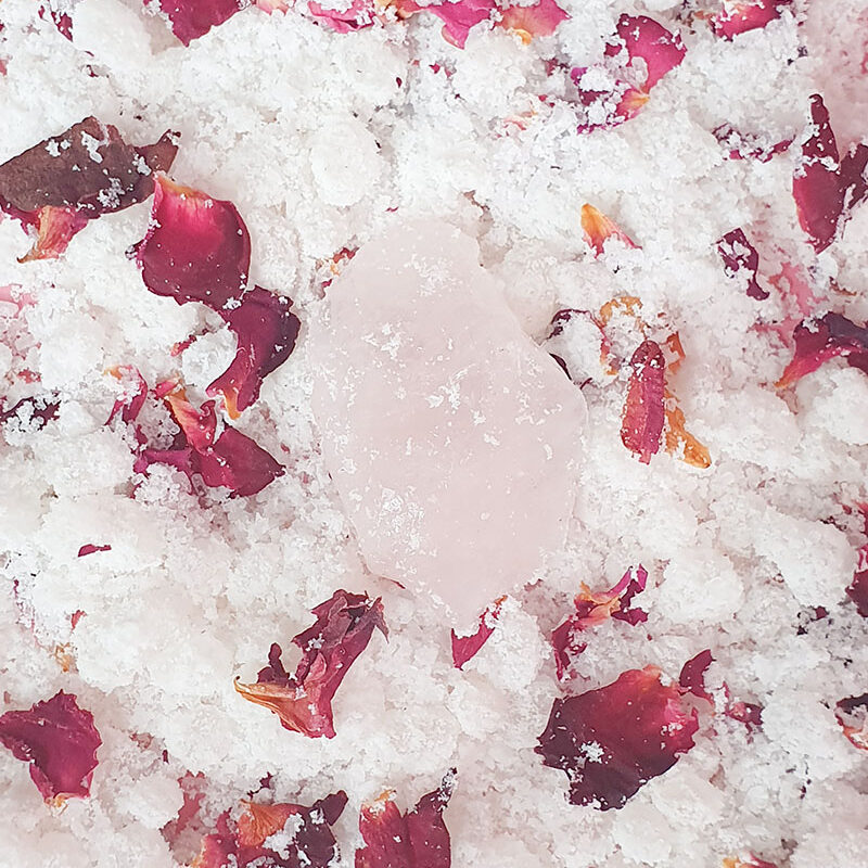An up close image of Bath Salts with pink rose petals and a chunk of rose quartz